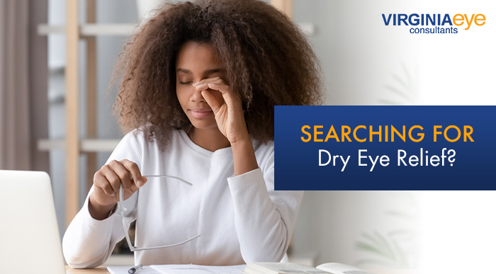 Black female model rubbing her eyes after taking off her glasses while she works on a laptop.
