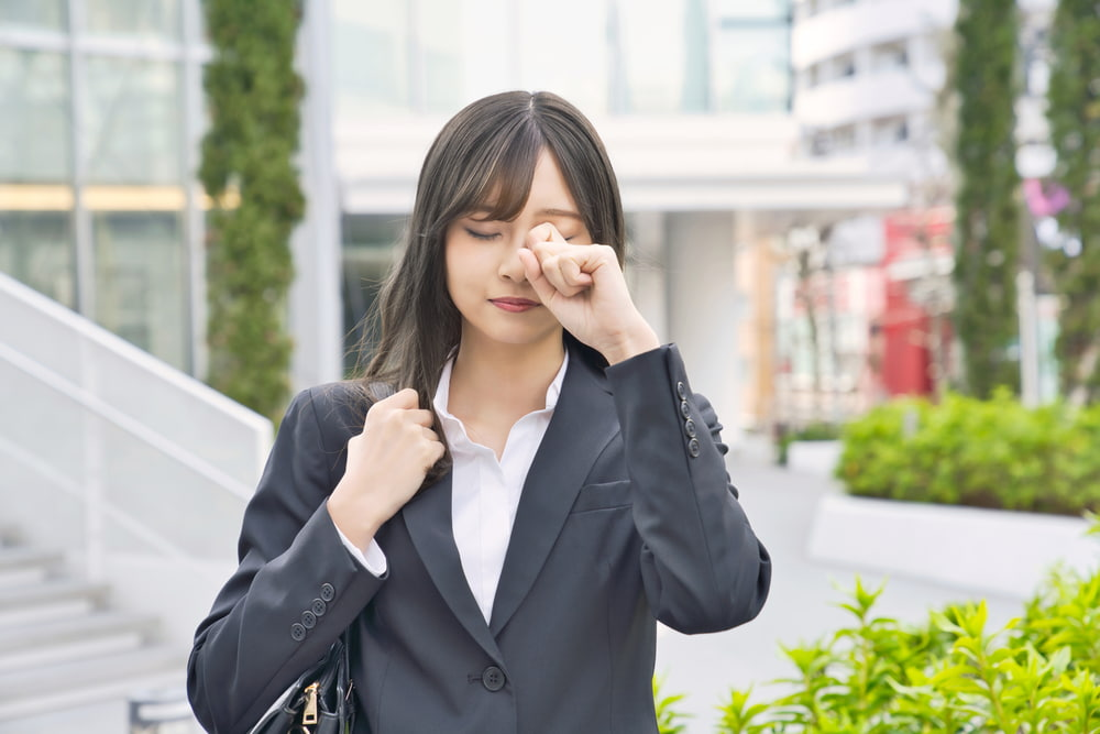 woman rubbing her eye on her way to work