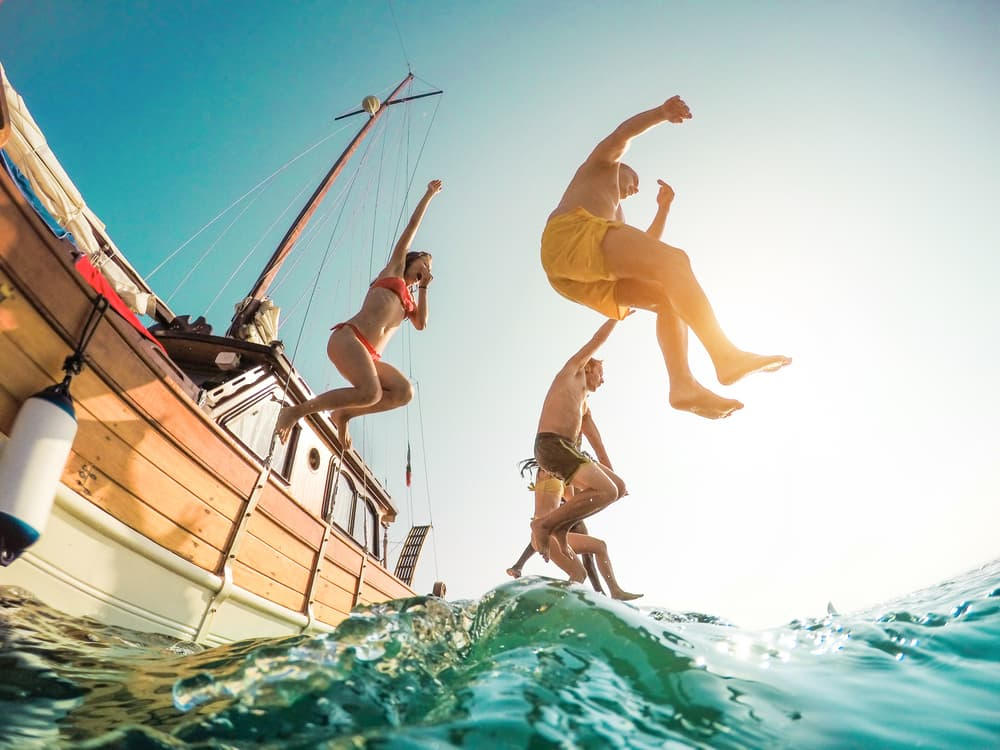 group of friends jumping off a boat into the ocean