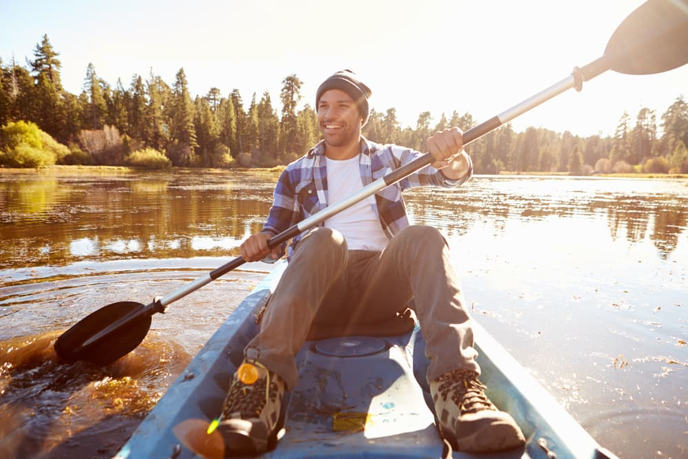 happy man kayaking on a lake
